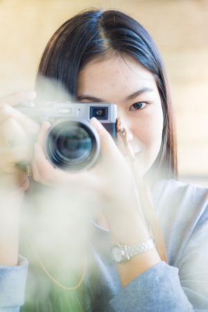 forground: Asian beautuful women use camera totke photo forground blurred, Close up