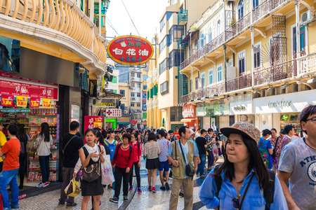 most: Macau, China - October 22, 2015: Tourists and shoppers walking along a narrow street with colourful building in central Macau with many shops and restaurants. Editorial