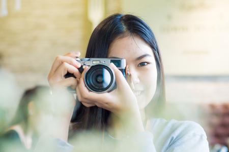 Asian beautuful women use camera totke photo forground blurred, Close up