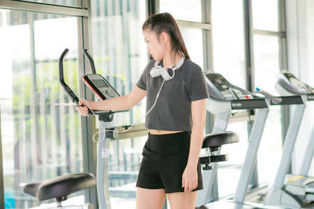 Beautiful fit asian woman exercising at the gym on bicycle fitness club