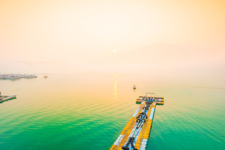 ridgeline: SUN MOON LAKE,TAIWAN - MARCH 21: Fog with many boats parking at the pier while sunrise on MARCH 21, 2015 at Sun Moon Lake, Taiwan. Sun Moon Lake is the largest body of water in Taiwan with nataral place.