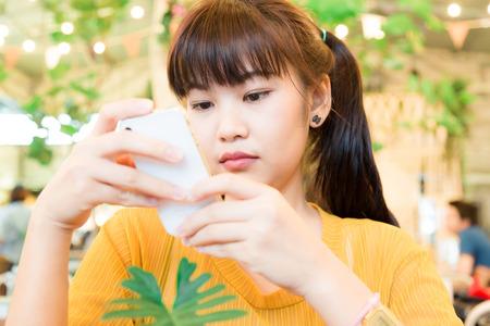 nerd girl: Portrait of asian beautiful nerd girl using mobile smart phone in cafe blurred background.