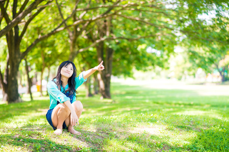 Women enjoying nature in green meadow with branch of tree, Freshness central park Stock Photo