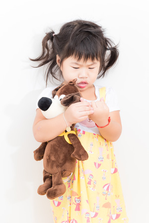 Little girl playing with her baby doll on white background