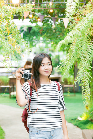 picture framing: Young asian woman making photos with vintage film camera at summer green park outdoor.