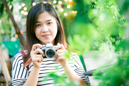 Young asian woman making photos with vintage film camera at summer green park outdoor.