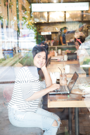 Hipster asian woman using laptop computer while sit in cafe Stock Photo