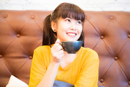Young pretty asian woman sitting at vintage luxury sofa drinking coffee and smiling