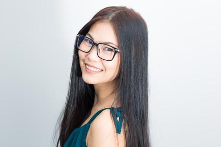 Portrait de la belle lunettes asiatiques femme sur blanc dans la chambre confortable