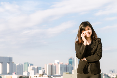 Executive working with a mobile phone on the roof top of office buildings in the background Stock Photo