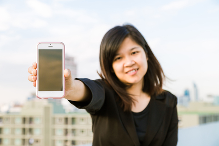 Happy Asian Businesswoman talking on smart phone with building background.