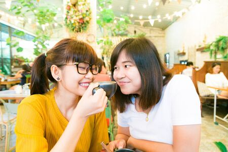 classy house: Smiling female asian friends holding coffee mugs while talking business at coffee loft store