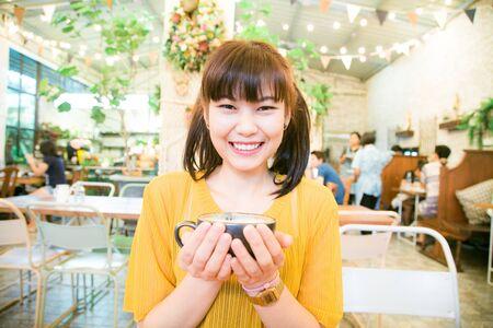 Smiling asian women sitting in art coffee shop holding latte  black mug