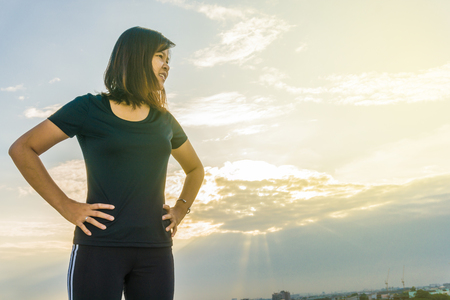 cardio workout: Fitness runner body closeup doing warm-up routine on roof top building before running, cardio workout. Stock Photo