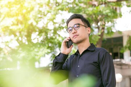 Happy young handsome man stand under tree outdoors and using smartphone for business talk, Glasses man