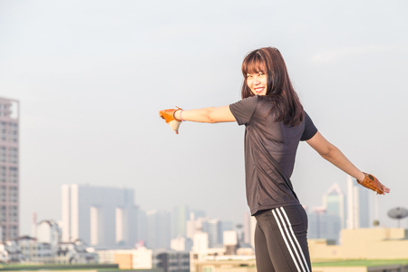 sports clothing: Asian female in sports clothing make body stretching before workout on building background.