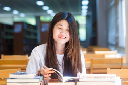 further: Portrait of a young attractive asian woman at the library sitting to reading a book. Education concept Editorial