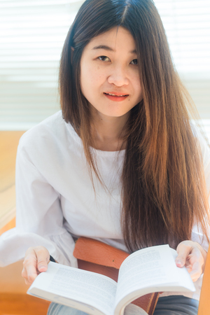 Portrait of a young attractive asian woman at the library sitting to reading a book. Education concept Stock Photo