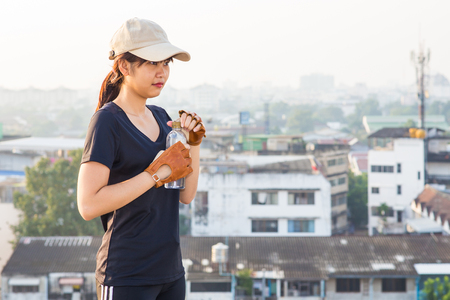 women sport: Asian sport women hold bottle of drinkking water after working out on the top of building