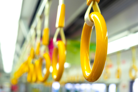 equilibrium: Yellow handrail holding bar inside of subway, Train transport