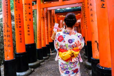 Woman dressed in traditional kimono japanese costume walking under tori gates at the fushimi-inari shrine, Kyoto Japan Editorial
