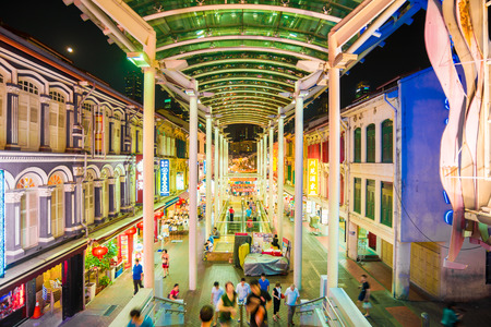 SINGAPORE - MARCH 5: Shoppers walk through a Chinatown market at night on March 5, 2015 in Singapore. The city states ethnic Chinese began settling in Chinatown circa 1820s.