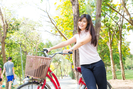 Smiling healthy asian women with bicycle in park, Summer vacation conept
