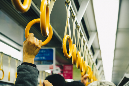 Hand of man holding on handle rail in train, Business transport