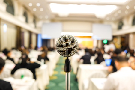 Close up of microphone in conference room soft and blur people for background Фото со стока