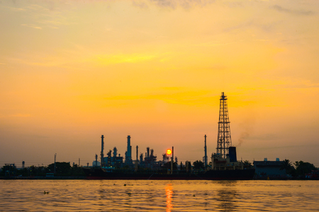 daybreak: Oil refinery petrochemical industry with river sunrise, Power industry Stock Photo