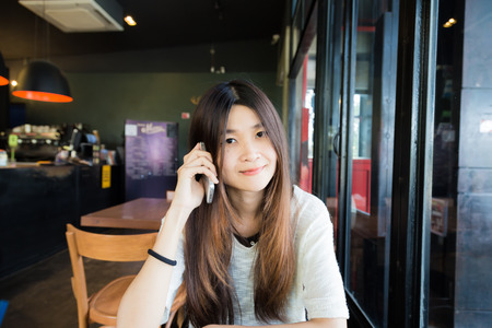 Asian beautiful women talking on smart phone while sitting in cafe, Business women with cellphone