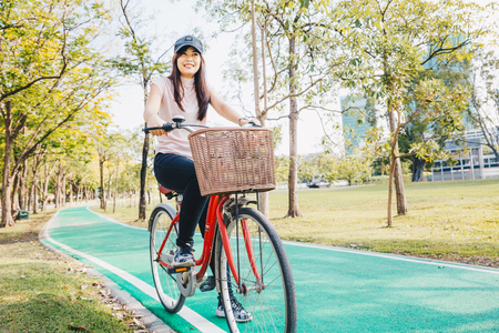 Asian active women with bicycle in city park, Sport and recreation