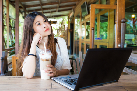 Women use laptop and drinking with ice coffee on wood table