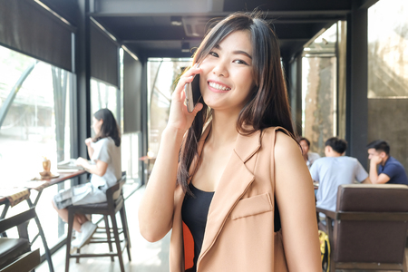 Business women in casual use cellphone for talking with customer in cafe, Business women in coffee shop