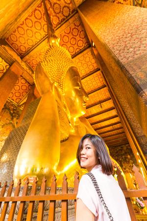 Asian tourist women post smiling on golden reclining buddha statue at Wat Pho temple, Bangkok Thailand