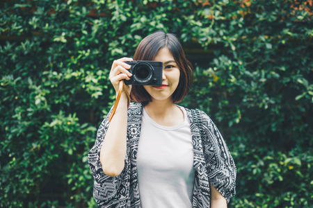 Hipster photographer women with camera on green leaf background