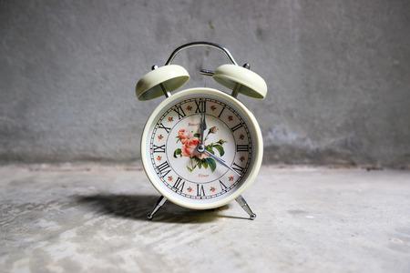 Old retro white cream alarm clock on floor vintage background Stock Photo