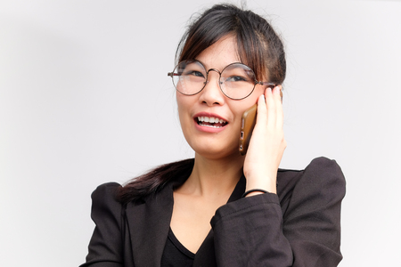 Las mujeres de negocios que hablan con smartphone usan traje y gafas aisladas sobre fondo blanco