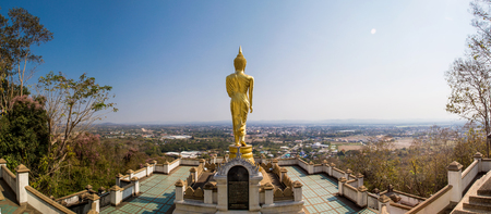 Panorama view of gold buddha monk statue on the mountain with city background
