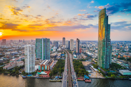Bangkok cityscape aerial view colorful sunset business district with river bridge Thailand