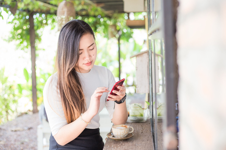 Business asian women texting on smart phone in modern coffe shop with coffee cup Foto de archivo
