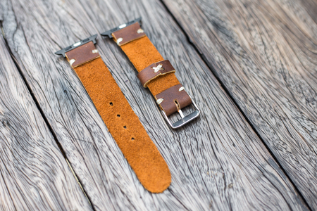 Part of leather smart watch wrist strap on wood table Stock Photo