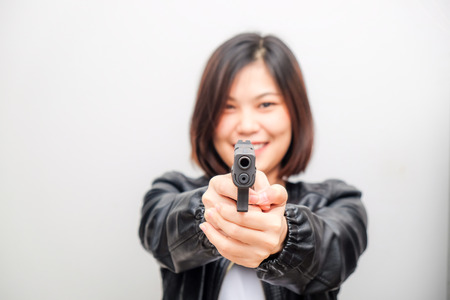 Black shirt women aiming gun to audience on white background, Defense personal trainning