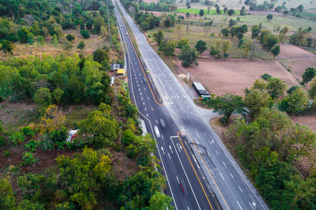 Road in green tree forest landscape vehicle movement aerial view