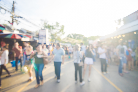 Blurred crowd of anonymous people walking on outdoor street market for shopping Stock Photo