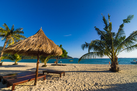 Wooden beach chairs with nature dry plant umbrella on white sand beach
