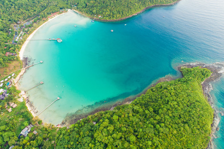 Exotic idyllic sea island with green tree forest aerial view