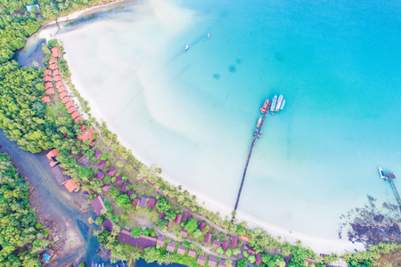 Aerial sea view of beautiful curve beach with wooden pier blue ocean