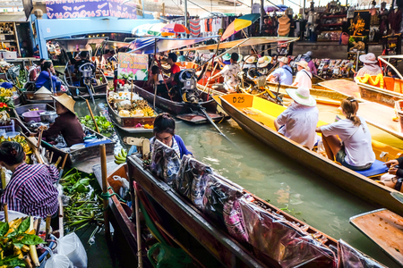 BANGKOK – MARCH 18: People shopping food from wooden boats at Amphawa floating market on March 18, 2018 in Bangkok. Traditional popular method of buying and selling Souvenir in Amphawa canals of Thailand.
