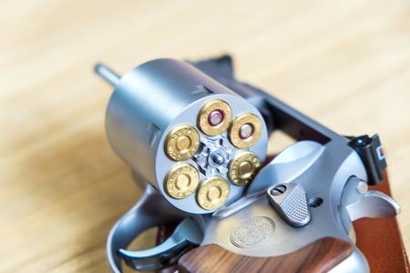 .357 .44 pistola revolver magnum con proiettile su sfondo di legno munizioni oggetto